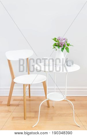 Elegant interior with white table and chair decorated with a bouquet of lilacs.