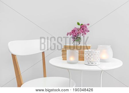 Candle lights books and flowers on a white table. Elegant home decor.