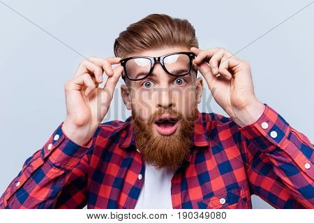 It's Incredible! Close Up Portrait Of Young Bearded Man Touching The Spectacles And Keeping His Mout