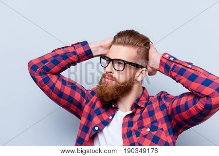 Stylish Confident Young Bearded Man In Checkered Shirt And Glasses Touching His Haircut Against Gray