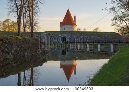 Kuressaare castle tower with bridge over the moat in sunset light. Water with reflections on foreground.