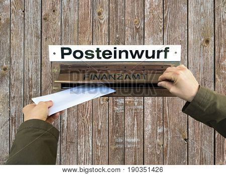 Two hands post a letter into the letterbox of the finance office. German Finanzamt.