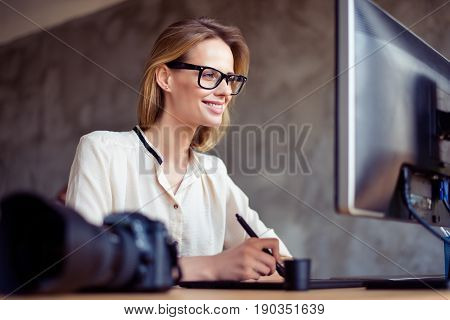 Smiling Happy Woman In Glasses Sitting At The Table In Front Of Computer Screen And Retouching New P