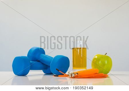 healthy eating concept. Small dumbbells. Apple juice. The skipping rope. Measuring tape waist. Green apple on a white background. healthy lifestyle. sport