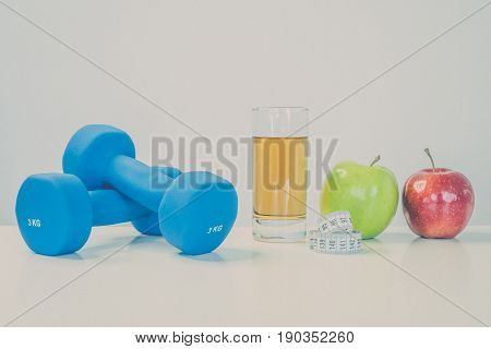 healthy eating concept. Small dumbbells. Apple juice. The skipping rope. Measuring tape waist. Green apple red apple on a white background. healthy lifestyle. sport