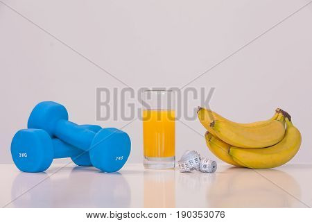 The concept of a healthy diet. Small dumbbells. Apple juice. Skipping rope. Measuring tape. Bananas. on a white background. healthy lifestyle. sport. Fitness food.