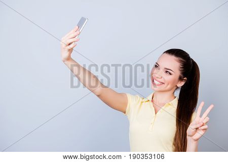 Selfie Mania! Young Cheerful Brunette In A Casual Yellow Tshirt Is Showing V-sign While Taking A Sel