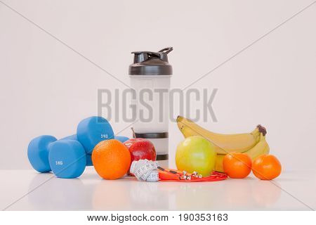 The concept of a healthy diet. Fintes meals. Sport lifestyle. Dumbbells. Shaker. Oranges. Apples. Bananas. fruit juice. The skipping rope. Measuring tape waist. on a white background. studio shooting.