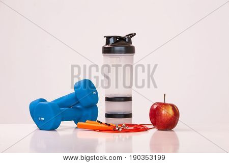 The concept of a healthy diet. Fintes meals. Sport lifestyle. Dumbbells. Red Apple. shaker. The skipping rope. on a white background