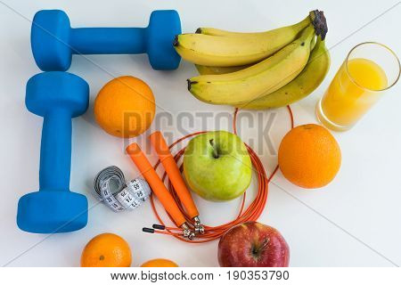 healthy eating concept. Dumbbells, skipping rope, bananas, oranges, measuring tape waist, oranges, red apple, green apple, orange juice on a white table. healthy lifestyle. sport. Fitness diet. view from above