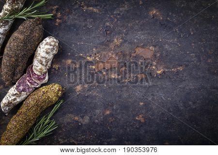 Traditional French Salami as top view on old rusty metal sheet