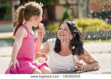 Mother making her cute little smiling daughter lick an ice-cream
