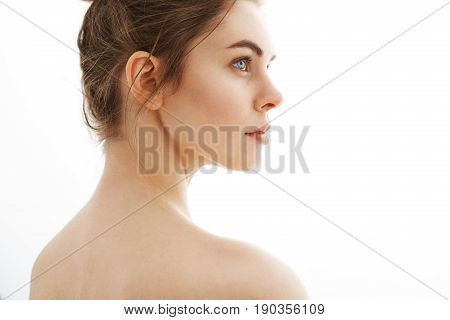 Portrait of young beautiful tender nude girl with bun standing back to camera over white background. Copy space.