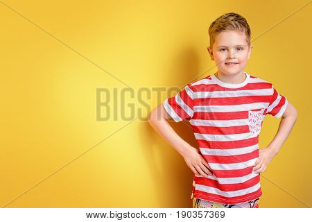 Portrait of a cute boy over bright yellow background. Clothes for children. Kid's fashion.