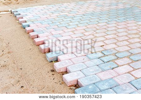 Colored brick paving stones in construction process. Outdoors horizontal image.