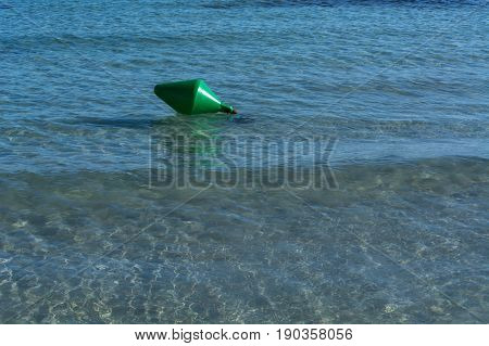 Green buoy as a shipping sign or sea sign in the sea.