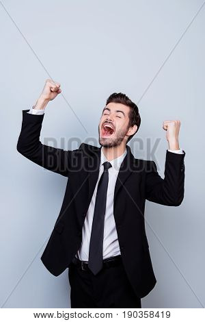 Vertical Portrait Of Happy Screaming Employer Triumphing With Raised Fists Against Gray Background
