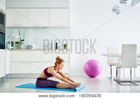 Portrait of fit red haired woman doing yoga exercises at home on floor: stretching before practice