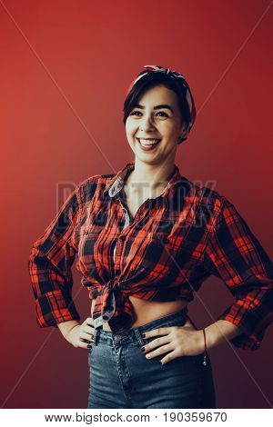 beautiful young woman isolated on red in studio in old fashion clothes representing pinup and retro style