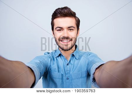 Handsome Brunet Young Man Is Making Selfie And Smiling. He Is Wearing Jeans Shirt And Behind Him Is