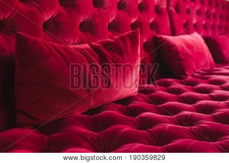 Textured surface of sofa with velour tapestry of red color close-up