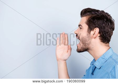 Side View Of Young Man Shouting Isolated On Light Blue Background Holding His Hand Near The Face
