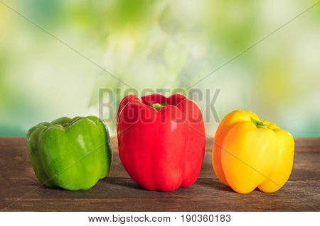 A side view of vibrant colourful fresh bell peppers on a dark rustic texture and a blurred green leaves background