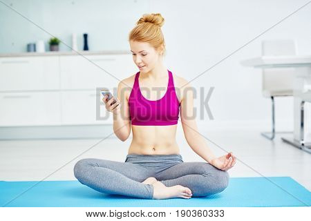 Portrait of fit red haired woman doing yoga exercises at home: using smartphone  sitting in lotus position  with legs crossed