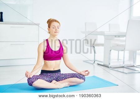 Portrait of fit red haired woman doing yoga at home: sitting in lotus position with eyes closed doing  breathing exercise and relaxing