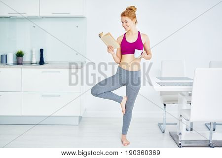 Portrait of fit red haired woman doing yoga exercises at home and reading book, smiling