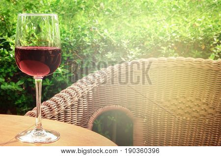 A glass of red wine on a terrace, on a blurred background of a rattan chair and green plants. Selective focus and a place for text