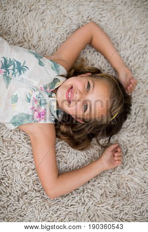 Portrait of smiling girl lying on rug in living room at home