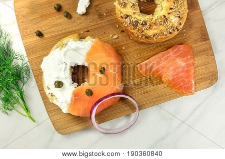 Bagel ingredients. Lox, purple onions, capers, dill, and the buns, shot from above on a wooden board and a white marble background in the process of making, with a place for text