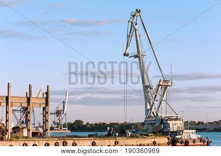 Floating cargo crane on barge near quay. Mooring in Riga. Outdoors.