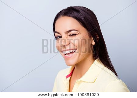 Successful smiling latino mulatto girl is winking on light blue background. She has a beaming smile!