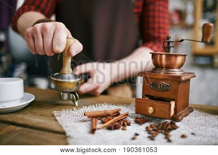 Closeup shot of barista working in retro coffee shop: pressing fresh grains with tamper after grinding them in antique mill