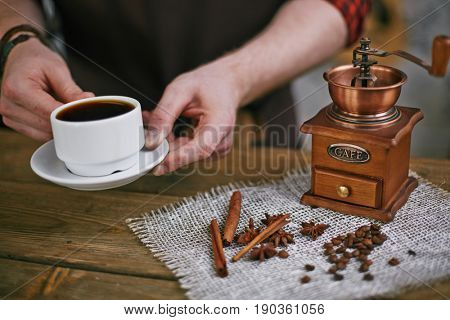 Closeup shot of barista working in retro coffee shop: holding cup of dark espresso next to  antique mill