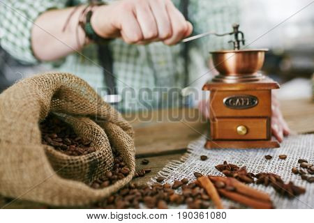 Closeup shot of old-fashioned man making coffee, grinding beans using small wooden mill