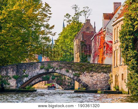 Town water canals with tourist boats in the historical center of Bruges, aka Brugge, Belgium, Europe.