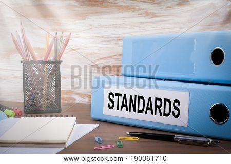 Standards, Office Binder on Wooden Desk. On the table colored pencils, pen, notebook paper.