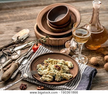 Old-fashioned dishware with pasta that looks rustic sitting on table, bottle of wine and bowl of salt