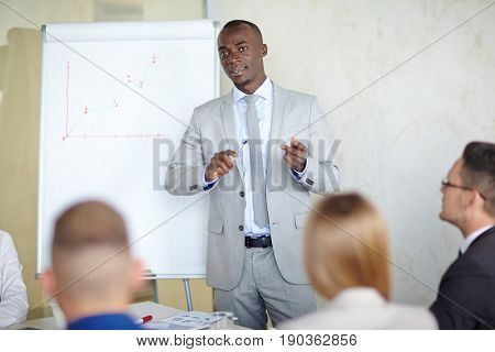Handsome African American entrepreneur explaining business plans to his employees while having business meeting in board room