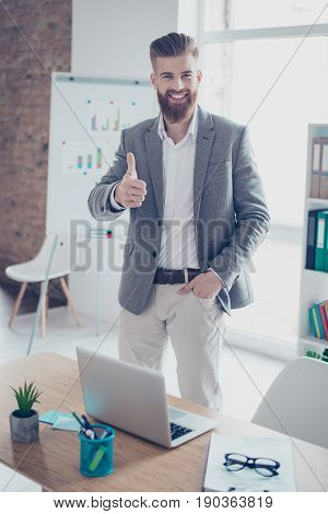 Successful Young Man Is Showing Thumb Up In Office. He Is Glad The Company`s Strategy Succeed