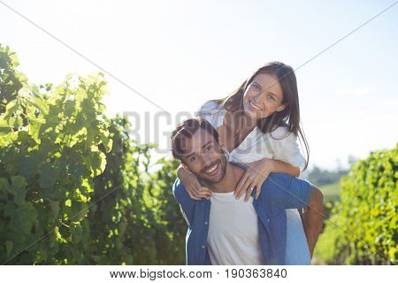 Portrait of happy young couple piggybacking at vineyard during sunny day
