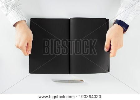 Man learning and writing on notebook. top view