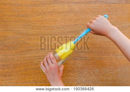 Female hands washing bottle brush on the table.