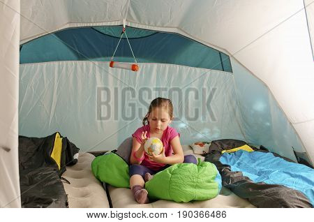 Little caucasian girl (elementary age) in the tent watching terrestrial globe. Summer adventure active recreation and touristic concept.