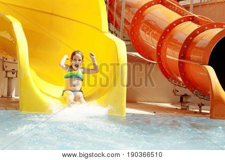 Happy little caucasian girl on waterslide of water park. Summer sunny day.