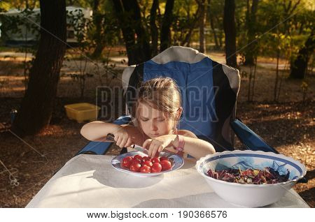 Little caucasian girl (elementary age) preparing a vegetable salad outdoor in the summer sunny evening. Summer camping active recreation touristic and education concept.