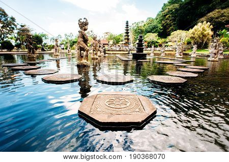 Water Palace Tirta Gangga on Bali island Indonesia. Labyrinth of decorated stone steps on the water in an artificial lake with statues on a background. Wide angle.